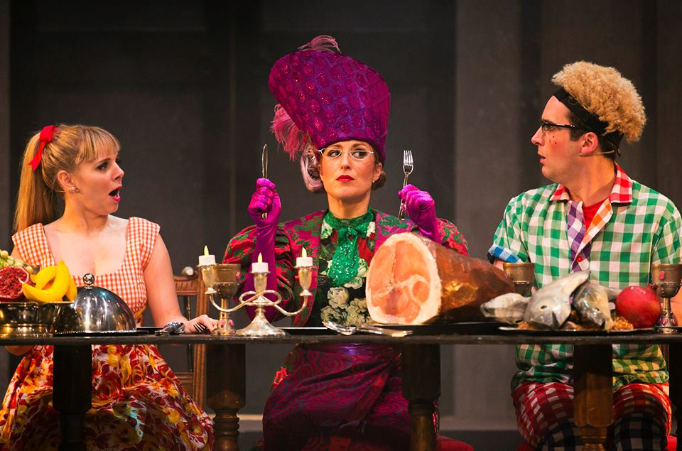 Actors Michelle Gallacher, Robert Jack and Dawn Sievewright are sat at a table wearing cheerful costumes designed by Alison Brown Costume Designer. Michelle wears purple and a large purple hat. She is holding up cutlery in front of a large ham.