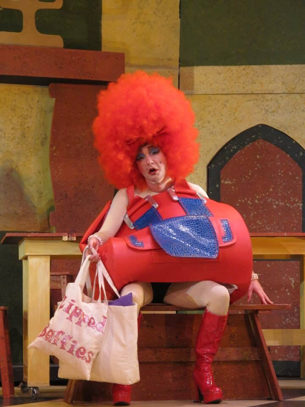 Actor Richard Conlon plays the part of an ugly sister in Cinderella. He is dressed in a huge red afro wig and red giant handbag costume designed by Alison Brown Costume Designer.