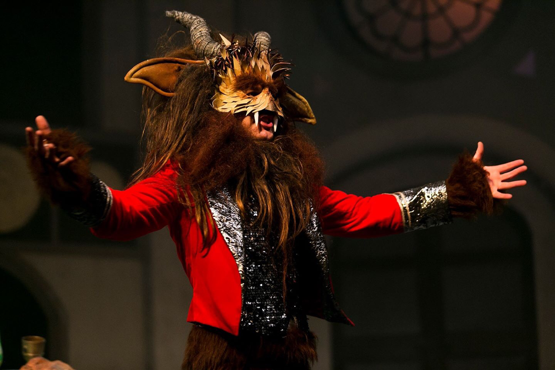 The Beast serenades Beauty in a red velvet jacket and textured mask with big ears and horns. Costumes designed by Alison Brown Costume Designer.