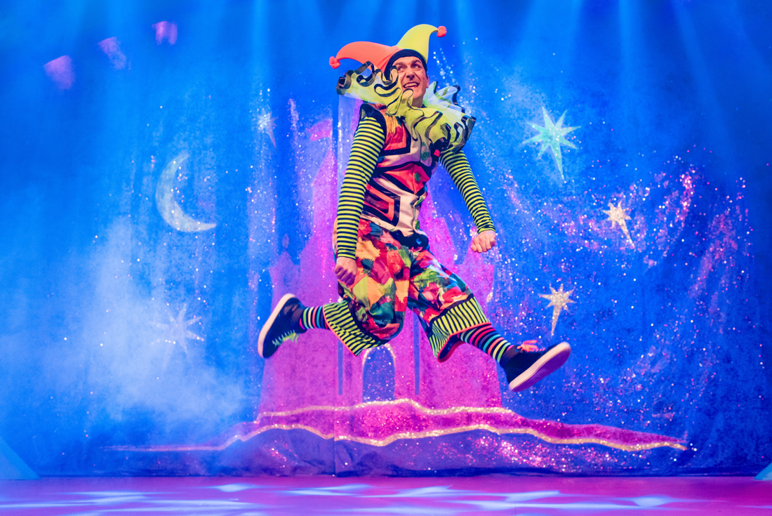 Actor Robert Jack leaps into the air in a colourful patterned jester's costume designed by Alison Brown Costume Designer.