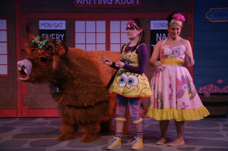 2 actors in panto wearing fun, colourful dresses are standing beside a panto Highland Cow. costumes designed by Alison Brown Costume Designer.